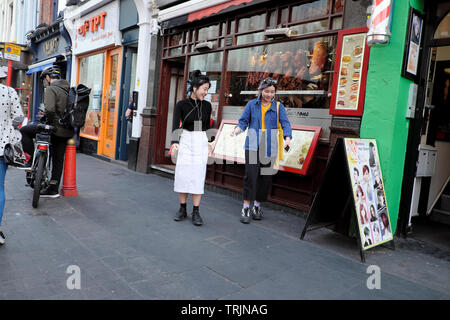 Two young female women friends walking past a Chinese restaurant on Wardour Street in Chinatown London W1 England UK   KATHY DEWITT - Stock Photo