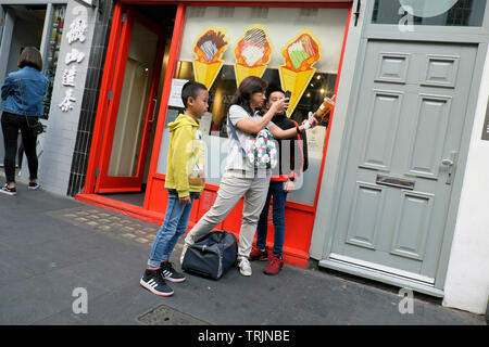 Mother and sons photograph plastic cup and straw outside Bubblewrap shop on Wardour Street in Chinatown London W1 England UK   KATHY DEWITT - Stock Photo