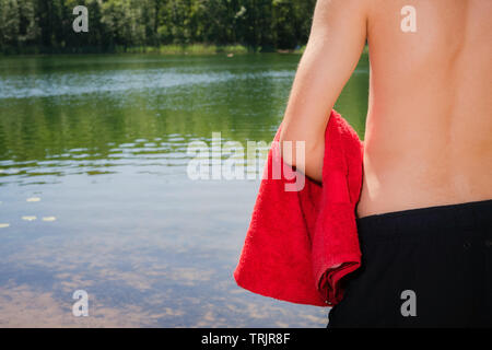 Young and fit, athletic male man standing on the lake shore without a shirt while holding red towel. Swimming, summer activities in nature - Stock Photo