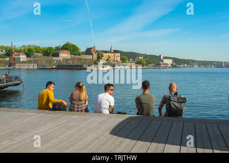 Friends talking, view on a summer afternoon of Norwegian friends relaxing along the Aker Brygge waterfront in Oslo harbor, Norway. - Stock Photo