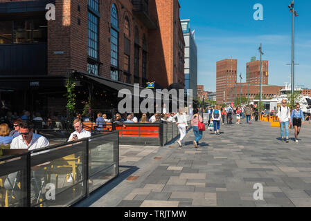 Oslo Aker Brygge, view of people relaxing on a summer afternoon on the Stranden - a waterfront promenade in the Aker Brygge harbour area of Oslo. - Stock Photo