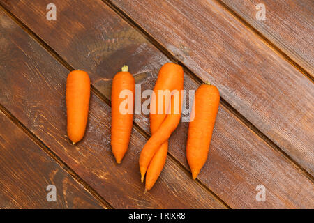 One ugly organic carrot among other normal carrots on wooden background. Zero waste concept. - Stock Photo