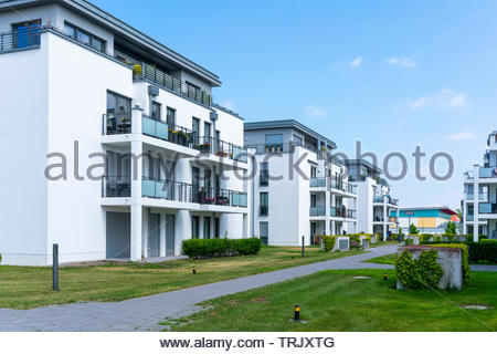 real estate modern apartments and penthouses surrounded by grassy areas - Stock Photo