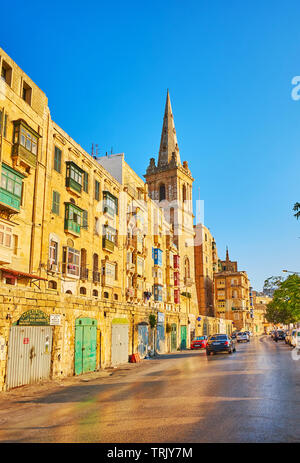 VALLETTA, MALTA - JUNE 19, 2018: Walk along the old residential buildings in Marsamxett road to the St Paul Pro-Cathedral with its tall stone bell tow - Stock Photo