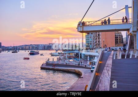 SLIEMA, MALTA - JUNE 19, 2018: The picturesque evening in resort with a view on harbor with ships, fiery sky and comfortable coastal promenade of Tign - Stock Photo