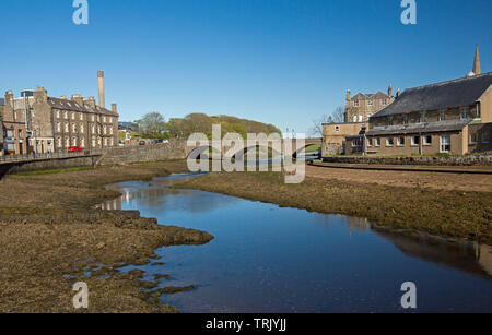Town of Wick in Caithness Scotland with buildings beside river and bridge, and blue sky reflected in calm water - Stock Photo