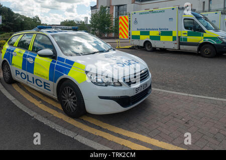 A Police Car and an Emergency Ambulance parked outside the Accident and Emergency Unit of University Hospital, Wishaw, North Lanarkshire, Scotland, UK - Stock Photo
