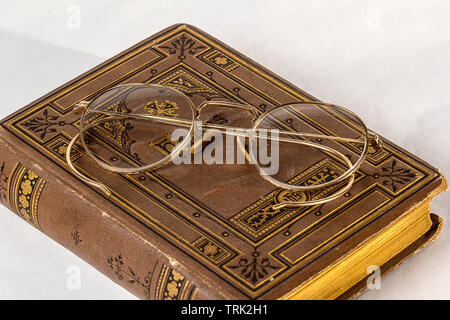 A pair of Antique Eyeglasses sitting on a vintage hymnal on a white background. - Stock Photo