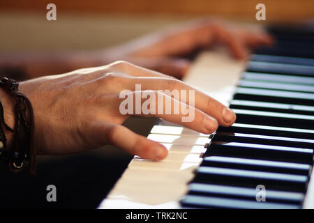 Hands, one of which is wearing a bracelet, playing a melody on a keyboard musical instrument - Stock Photo