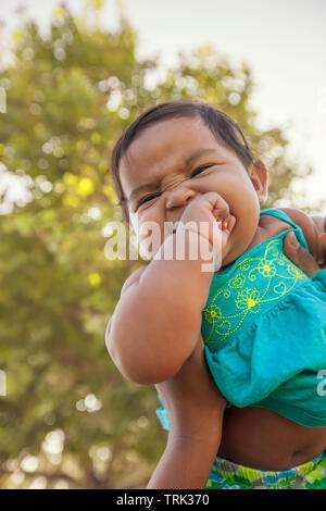A happy and excited baby girl bites her own hand as she is lifted up into the sky by her mother who holds her tightly from below. - Stock Photo