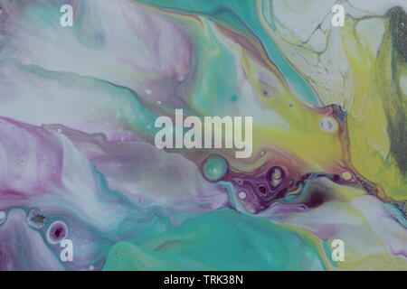 Closeup of an acrylic pour painting done in teal, magenta, yellow, violet, and white that resembles the Aurora Borealis. - Stock Photo