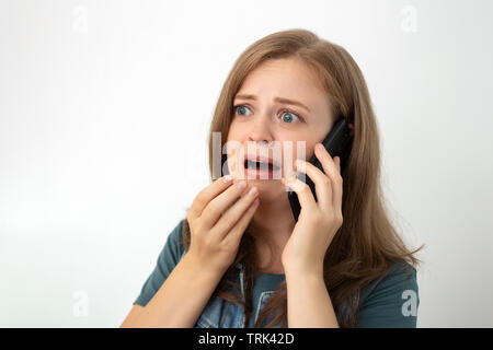 Young caucasian girl woman is talking on the mobile phone, looks scared or sad - Stock Photo