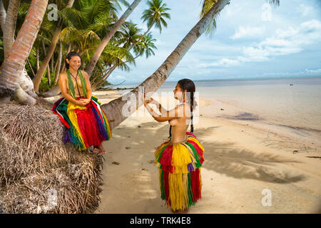 Two young girls (MR) is in traditional outfit for cultural cerimonies taking a photo with a smartphone on the island of Yap, Micronesia. - Stock Photo