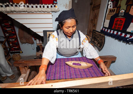 A woman weaving with spindle and loom in Peguche, a village of weavers near Otavalo, Ecuador, South America. - Stock Photo