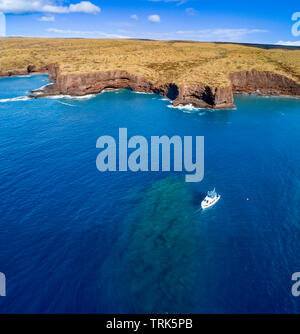 An aerial view of a dive charter vessel anchored at 2nd Cathedral, a popular site off the south shore of the island of Lanai, Hawaii, USA. - Stock Photo