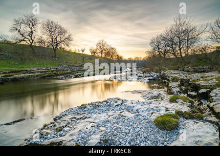 Colourful sunset sky over flowing water of River Wharfe & rocky limestone riverbanks - by scenic Ghaistrill's Strid, Grassington, Yorkshire Dales, UK. - Stock Photo