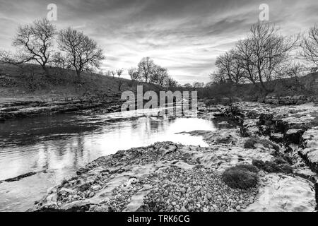 B & W dramatic cloudy sky, flowing water of River Wharfe & rocky limestone riverbanks - by scenic Ghaistrill's Strid, Grassington, Yorkshire Dales, UK - Stock Photo
