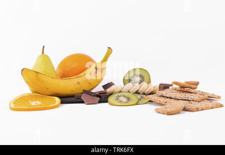 A mix of sliced kiwis and oranges, whole banana, chocolate and chocolates chips on a bright background - Stock Photo