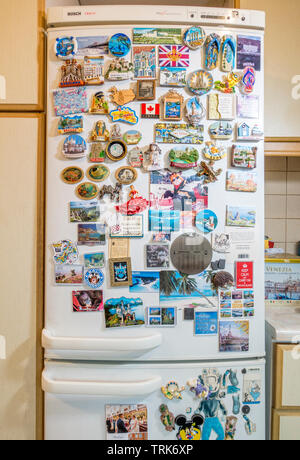 Decorative magnets from places visited and various words of wisdom, attached to the door of a fridge / freezer in a domestic kitchen. - Stock Photo