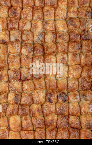 A piece of Bosnian style burek. It is a pastry filled with seasoned meat and onions and baked in an oven. Traditional Bosnian pastry- manti borek. - Stock Photo