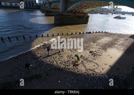 Mudlarkers searching the bank of the River Thames under Southwark Bridge - Stock Photo