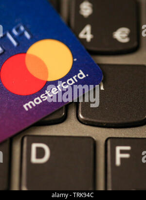 Bucharest, Romania - May 14, 2019: Macro image with the details of a Mastercard plastic credit card with the Mastercard logo on a laptop keyboard - on - Stock Photo