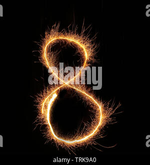 burning sparkler stick and writing sparkling text . number eight isolated on black background