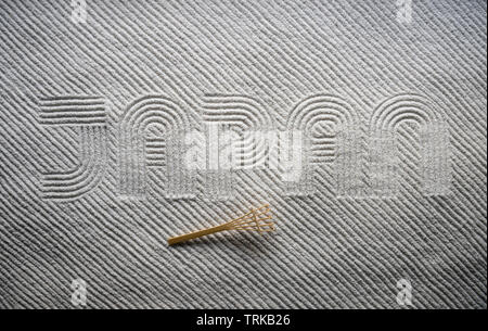 Small wooden rake sits on Japanese Zen garden raked with the word JAPAN in capital letters in textured white sand - Stock Photo