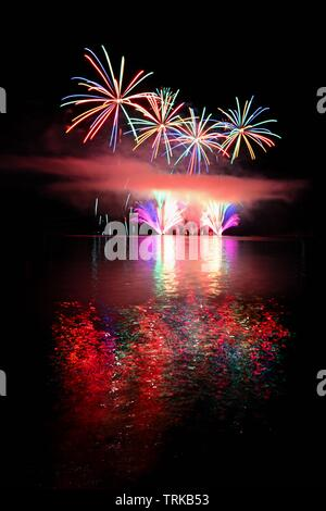 Beautiful colorful fireworks on the water surface. Night scene. Concept for holidays and celebrations. - Stock Photo