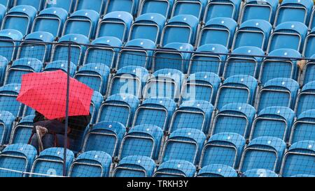 Surbiton, London: A single fan battles the rain in hope of seeing some tennis action later in the day at the 2019 Surbiton Trophy. - Stock Photo