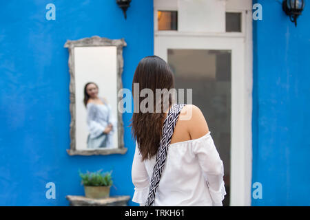 Beautiful woman on white dress looking at herself on a mirror on the colorful streets of the colonial walled city of Cartagena de Indias - Stock Photo