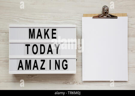 'Make today amazing' words on a light box, clipboard with blank sheet of paper on a white wooden background. From above, overhead, flat lay, top view. - Stock Photo