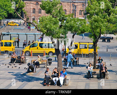 Istanbul, Turkey - 05/26/2010: People sitting on benches at bosporus strait coast, yellow taxis trees, canons replicas, sunny day. - Stock Photo
