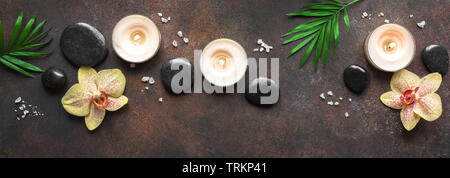 Spa concept on dark background, palm leaves, candles and zen like black stones, top view, banner. Spa composition. - Stock Photo