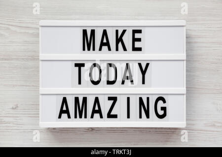 'Make today amazing' words on a modern board on a white wooden background. From above, overhead, flat lay, top view. Closeup. - Stock Photo