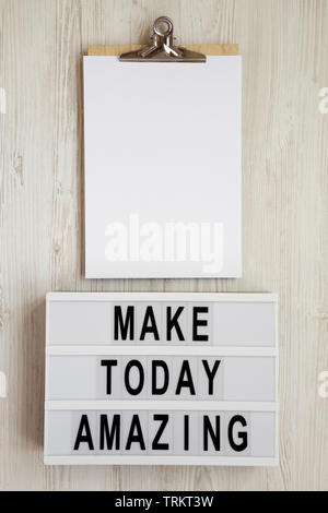 'Make today amazing' words on a modern board, clipboard with blank sheet of paper on a white wooden surface. From above, overhead, flat lay, top view. - Stock Photo