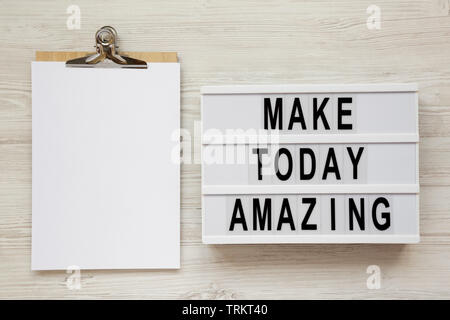 'Make today amazing' words on a lightbox, clipboard with blank sheet of paper on a white wooden background. From above, overhead, flat lay, top view. - Stock Photo