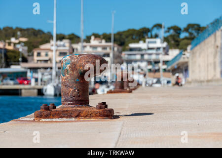 Old mooring bollard part of the harbour in Cala Ratjada, Spain. - Stock Photo