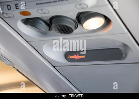 Aircraft passenger cabin lights, warning lights, and seat lettering - Stock Photo