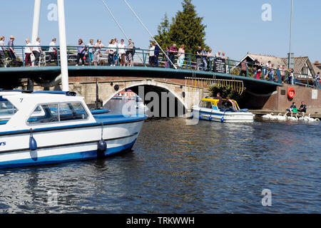 A small launch approaches the historic Wroxham Bridge. Day launches are a popular way of exploring the Broads on a day visit. - Stock Photo