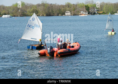 Sailing is a popular pastime on the Norfolk Broads and here a safety boat keeps watch on young novice sailors on Wroxham Broad. - Stock Photo