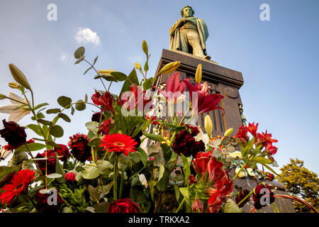Flowers at the monument to Alexander Pushkin to 220 birthday of the poet on Pushkin square in the center of Moscow, Russia - Stock Photo