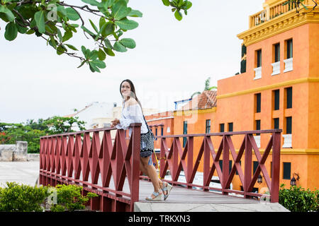 Beautiful woman on white dress standing alone at the walls surrounding of the colonial city of Cartagena de Indias - Stock Photo