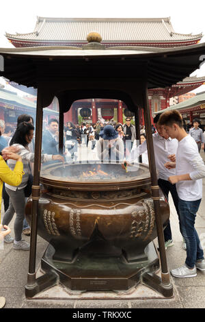 Woman praying in front of a smoking Shrine in Tokyo, Japan - Stock Photo