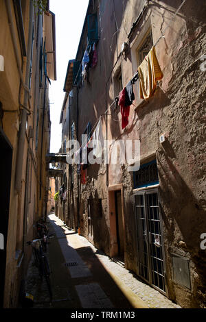 Albenga old town street view, with clothes line. Liguria, Italy. - Stock Photo