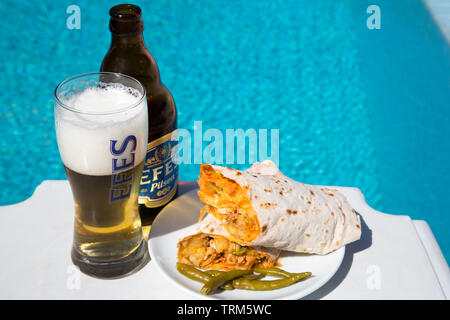 A plate of Turkish chicken kebab (Tavuk durum} served with a cold bottle of Efes pilsen beer on a sunny afternoon by the pool, Marmaris, Turkey - Stock Photo