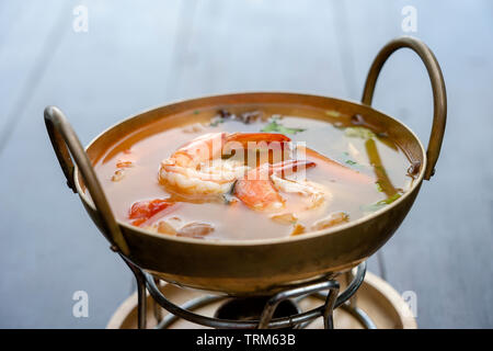 Tom yam kung or Tom yum, Tom yam is a spicy clear soup with shrimps, close up. Popular food in Thailand, thai cuisine - Stock Photo