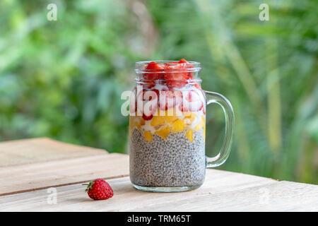 Almond milk chia pudding with fresh strawberries and mango in a glass jar mug. Vegan raw breakfast. Chia seeds and fresh cut fruits and berries desser - Stock Photo