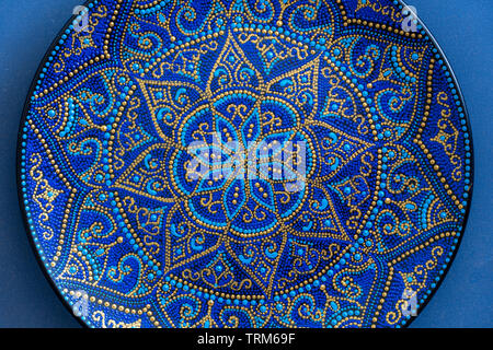 Decorative ceramic plate with blue and golden colors, painted plates, close up. Decorative porcelain plate painted with acrylic paints, handwork - Stock Photo