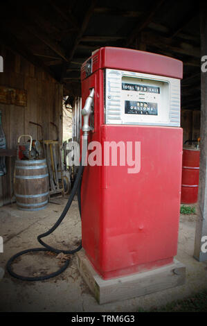 An old-fashioned gas pump in front of a rural corner store. - Stock Photo